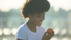 Aire libre fresco de la manzana de la consumición cabelluda rizada hermosa de la mujer, consumición sana, dieta almacen de video