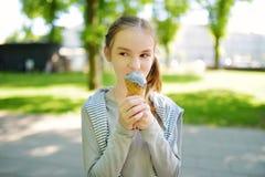 Aire libre fresco sabroso del helado de la consumición linda de la muchacha en día de verano soleado caliente imagen de archivo libre de regalías