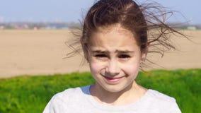 Aire libre hermoso que mira, pelo de la chica joven que sopla en viento en fondo de la naturaleza metrajes