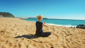 Aire libre practicante de la yoga de la mujer del ajuste en el día soleado Mujer joven meditating almacen de metraje de vídeo
