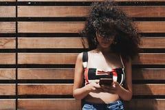 Aire libre rizado de la muchacha con el teléfono móvil y la cara cubiertos por el pelo foto de archivo