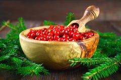 Airela, foxberry, arando, lingonberry em uma bacia de madeira com uma colher em uma tabela de madeira marrom Cercado por ramos do Foto de Stock
