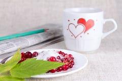 Airela no açúcar de encontro a uma caneca com corações Imagens de Stock Royalty Free