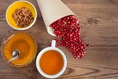 Airelles rouges, miel, noix et une tasse de thé dessus Images stock