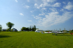 Airfield. A wide-angle shot of a glider airfield with planes, gliders, hangars, and barns in background.  All logos and registrations removed and resub with Stock Image