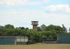 Airfield control tower hidden in forest with clouds Royalty Free Stock Image