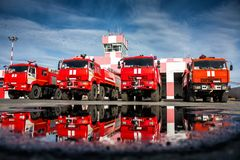 Airfield fire trucks with reflection in a puddle. Near garage boxes royalty free stock image