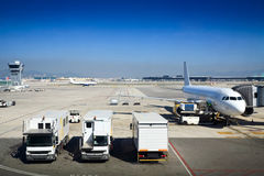 Airfield with planes and trucks. Barcelona El Prat airdrome. Planes, trucks, tower, terminals and runways Royalty Free Stock Image