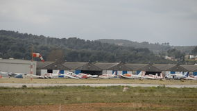 Airfield On A Windy Day. This is footage of an airfield in a gray windy days, the planes are staying on ground and the wind indicator si blowing out stock footage