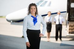 Airhostess With Hand On Hip Standing At Airport Stock Photos