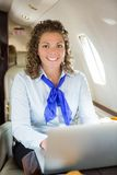 Airhostess With Laptop In Private Jet Stock Images