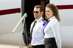 Airhostess And Pilot Looking Away Against Private Royalty Free Stock Photography