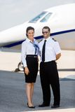 Airhostess And Pilot Standing Against Private Jet Stock Photo