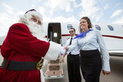 Airhostess And Pilot Welcoming Santa Against. Private jet at airport terminal Royalty Free Stock Photo