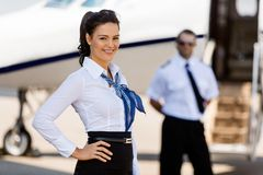 Airhostess Smiling With Pilot And Private Jet In. Portrait of attractive airhostess with pilot and private jet in background at terminal Royalty Free Stock Photo