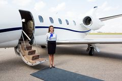 Airhostess Standing By Private Jet. Full length portrait of airhostess standing by private jet at airport terminal Stock Photography