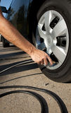 Airing up a car tire. A man airing up a car tire Stock Image