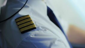Airline captain sitting in cockpit, adjusting uniform, getting ready for takeoff. Stock footage stock video