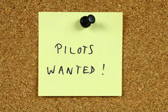 Airline career. Yellow sticky note pinned to an office notice board. Pilots wanted - airline employment and aviation career recruitment message royalty free stock photos