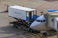 Airline catering. Catering truck docked to parked airliner, supplying food and drinks royalty free stock photography