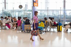 Airline female staff walks by seated Asian tourists inside Suvarnabhumi International AIrport terminal in Bangkok, Thailand royalty free stock image