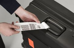 Airline luggage the destination tag. Airline luggage security tag being attached to a travellers black suitcase Royalty Free Stock Photos
