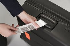 Airline security tag on a suitcase. Airline luggage security tag being attached to a travellers black suitcase Stock Photos