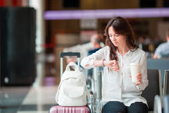 Airline passenger in an airport lounge waiting for flight aircraft. Caucasian woman looking for time in the waiting room Royalty Free Stock Images