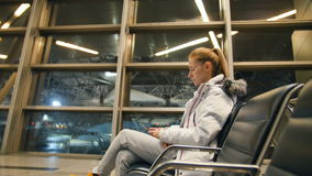 Airline passenger in an airport lounge waiting for flight aircraft. Caucasian woman with smartphone in the waiting room stock video