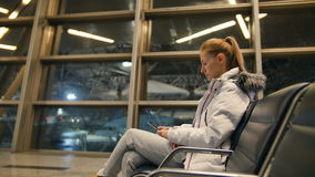 Airline passenger in an airport lounge waiting for flight aircraft. Caucasian woman with smartphone in the waiting room stock footage