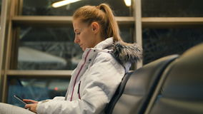 Airline passenger in an airport lounge waiting for flight aircraft. Caucasian woman with smartphone in the waiting room stock video footage