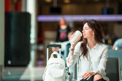 Airline passenger in an airport lounge waiting for flight aircraft. Caucasian woman with smartphone in the waiting room Royalty Free Stock Photography