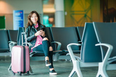 Airline passenger in an airport lounge waiting for flight aircraft. Caucasian woman with smartphone in the waiting room. Silhouette of passenger in an airport Stock Photos
