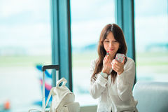 Airline passenger in an airport lounge waiting for flight aircraft and coloring lipstick. Caucasian woman with red Stock Photography