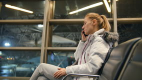 Airline passenger in an airport lounge waiting for flight aircraft and talk to the smartphone. Airline passenger in an airport lounge waiting for flight aircraft stock footage