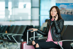 Airline passenger in an airport lounge waiting for flight aircraft talking by her smartphone. Caucasian woman looking at Stock Photos