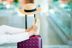 Young woman in an airport lounge waiting for landing. Closeup legs on the baggage. Airline passenger in an airport lounge waiting for flight aircraft stock photo