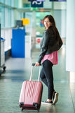 Airline passenger with baggage in an airport lounge waiting for flight aircraft. Young woman in international airport Stock Photos