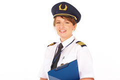 Airline pilot. Beautiful female airline pilot wearing uniform with epauletes and hat with golden wings standing isolated on white background stock photo