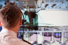 Airline pilot. Wearing uniform with epaulettes and headset working in airliner during flight royalty free stock image