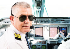 Airline pilot. Wearing uniform with epaulettes and headset working in airliner during flight stock images