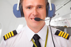 Airline pilot. Pilot wearing uniform with epauletes, inside airliner Stock Photos