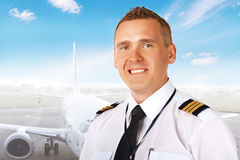 Airline pilot at the airport. Airline pilot wearing uniform with epaulettes with passenger aircraft in background royalty free stock photo