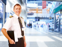 Airline pilot at airport. Airline captain pilot wearing uniform with epaulettes standing at airport with his flight documents royalty free stock image