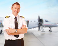 Airline pilot at the airport. Airline pilot wearing uniform with epaulettes with passenger aircraft in background stock image