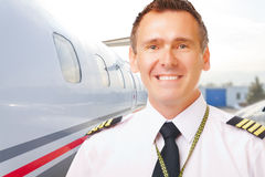 Airline pilot at the airport. Airline pilot wearing uniform with epaulettes with passenger aircraft in background royalty free stock photos