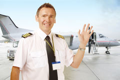 Airline pilot at the airport waving Stock Photos