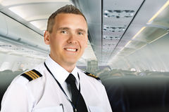 Airline pilot on board. Airline pilot wearing uniform with epaulettes on board of passenger aircraft stock photography
