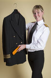 Airline pilot brushing uniform jacket. Attractive middle aged emale airline captain brushing her uniform jacket Stock Images