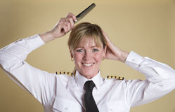 Airline pilot combing her hair Royalty Free Stock Images